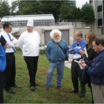 Chef Jason Saunders and Master Gardener Larry Kloze (center left and right) talk with others on garden planning committee at Good Samaritan at proposed garden site.